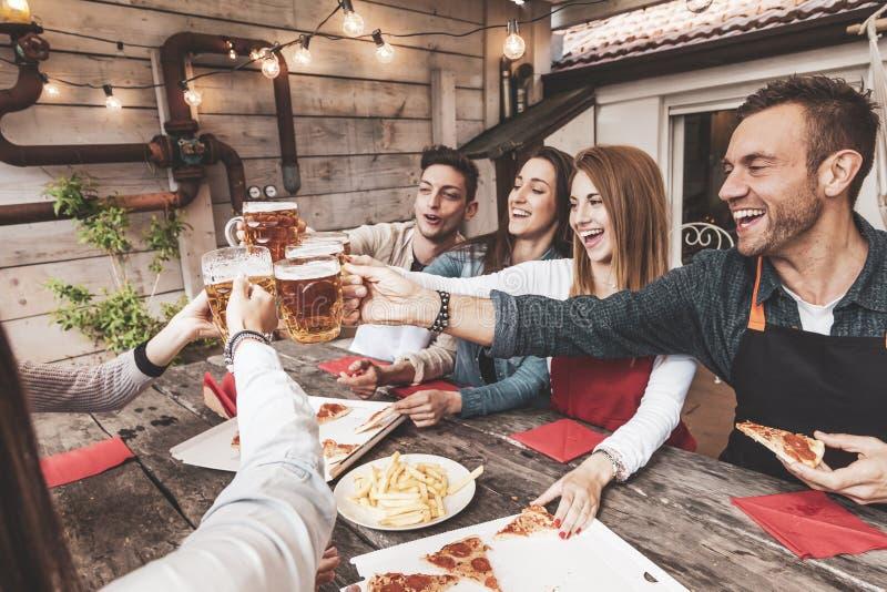Szcz??liwa grupa przyjaciele pije piwo i je pizz? obraz royalty free