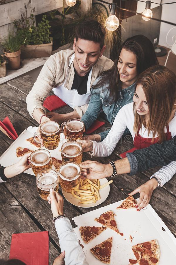 Szcz??liwa grupa przyjaciele pije piwo i je pizz? fotografia royalty free