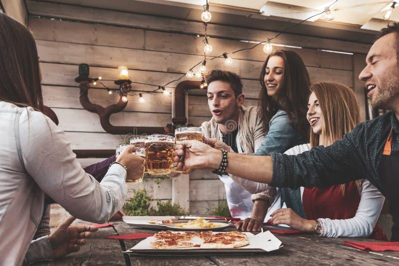 Szcz??liwa grupa przyjaciele pije piwo i je pizz? zdjęcie stock