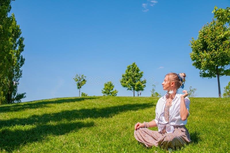 Szcz??liwa kobieta siedzi na trawa gazonie Pi?kna boho stylu kobieta z akcesoriami cieszy si? lato s?onecznego dzie? w parku obrazy stock