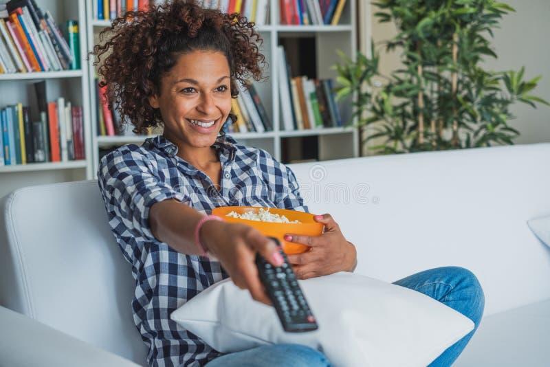 Szcz??liwa kobieta siedzi w domu z pilot do tv ogl?da tv obraz royalty free
