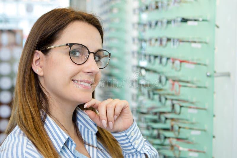Szcz??liwa kobieta wybiera szk?a przy optyka sklepem obrazy royalty free
