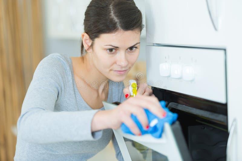 Szcz??liwa kobiety cleaning kuchenki kuchnia w domu obraz royalty free