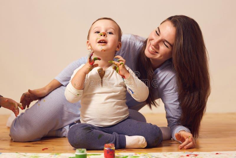 Szcz??liwa matka i jej ma?y syn z farbami na jego twarzy ubieraj?cej w dom?w ubraniach siedzimy na drewnianej pod?odze w fotografia stock