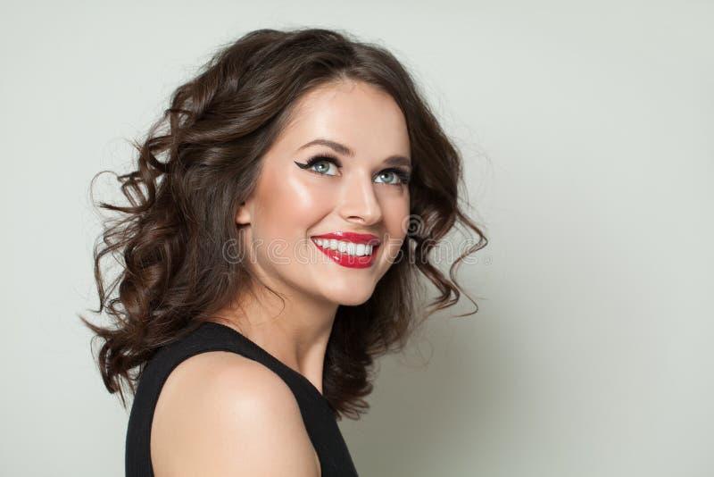 szcz??liwa portret kobiety Uśmiechnięta dziewczyna z makeup i brązu kędzierzawym włosy fotografia stock