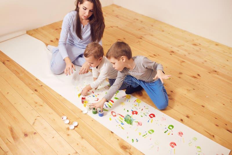 Szcz??liwa potomstwo matka i jej dwa ma?ego syna ubieraj?cych w dom?w ubraniach siedzimy na drewnianej pod?odze w pokoju i obrazy stock