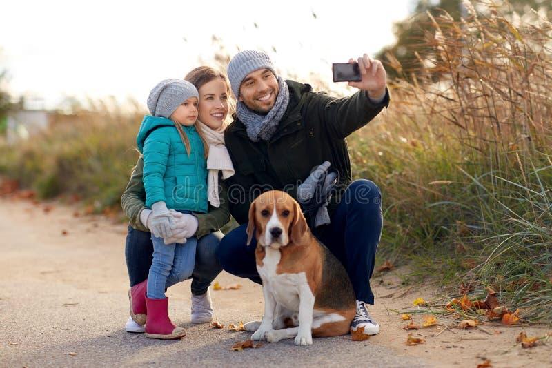 Szcz??liwa rodzina z psem bierze selfie w jesieni zdjęcie royalty free