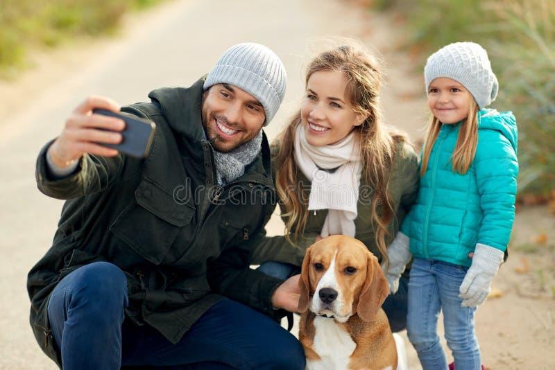 Szcz??liwa rodzina z psem bierze selfie w jesieni zdjęcia stock