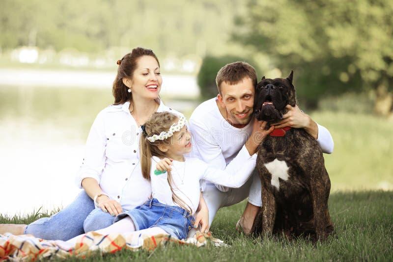 Szcz??liwa rodzina z zwierz? domowe psem przy pinkinem w Pogodnym letnim dniu pregn zdjęcia stock