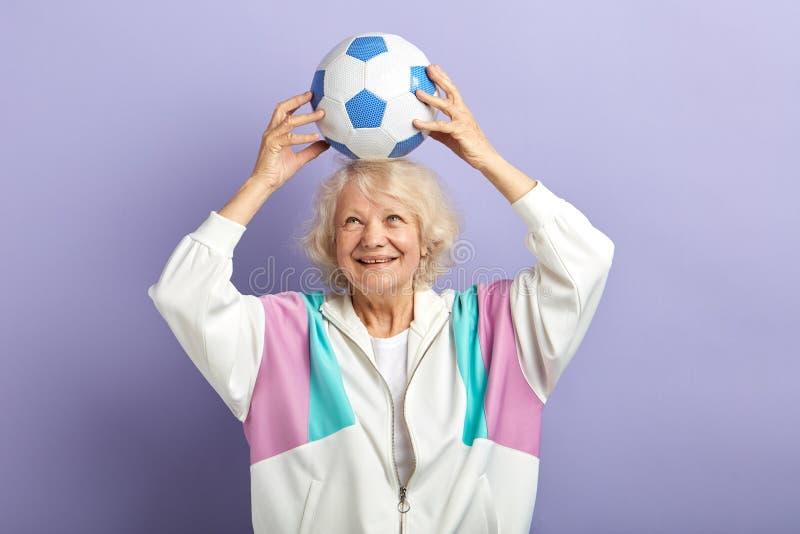 Szcz??liwa starsza kobieta utrzymuje futbolowy na g?owie w sportswear obraz royalty free