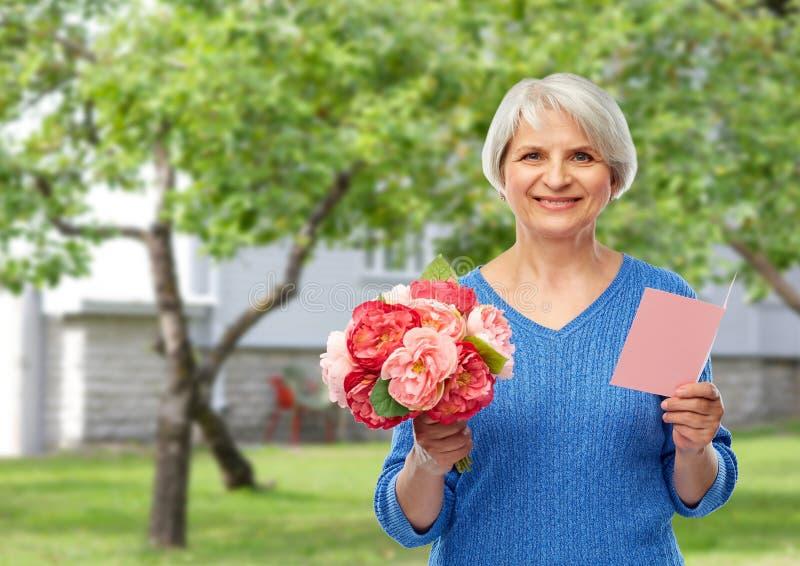 Szcz??liwa starsza kobieta z kwiatami i kartk? z pozdrowieniami zdjęcie stock