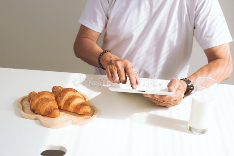 Szcz??liwa starsza para ma croissant ?niadanie i pije mleko w domu, dotyka na cyfrowej pastylce obraz stock
