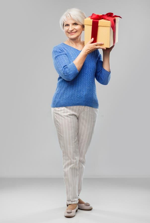 Szcz??liwa u?miechni?ta starsza kobieta z urodzinowego prezenta pude?kiem obraz royalty free