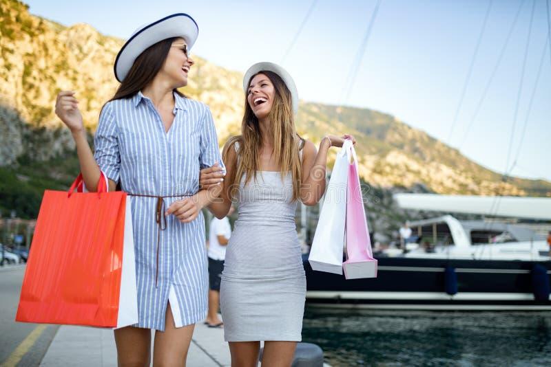Szcz??liwe m?ode kobiety z torbami na zakupy cieszy si? w zakupy Konsumeryzm, zakupy, stylu ?ycia poj?cie obrazy stock