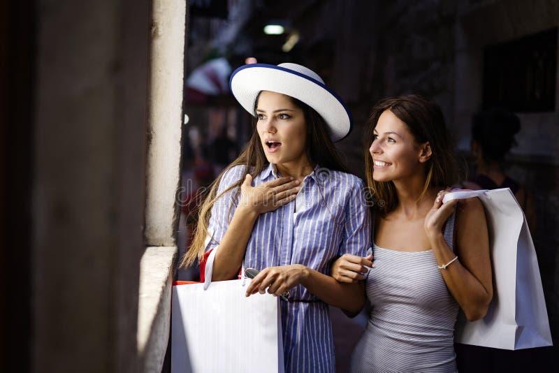 Szcz??liwe m?ode kobiety z torbami na zakupy cieszy si? w zakupy Konsumeryzm, zakupy, stylu ?ycia poj?cie fotografia stock