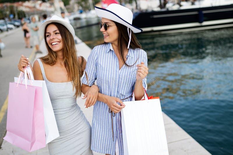 Szcz??liwe m?ode kobiety z torbami na zakupy cieszy si? w zakupy Konsumeryzm, zakupy, stylu ?ycia poj?cie zdjęcie stock