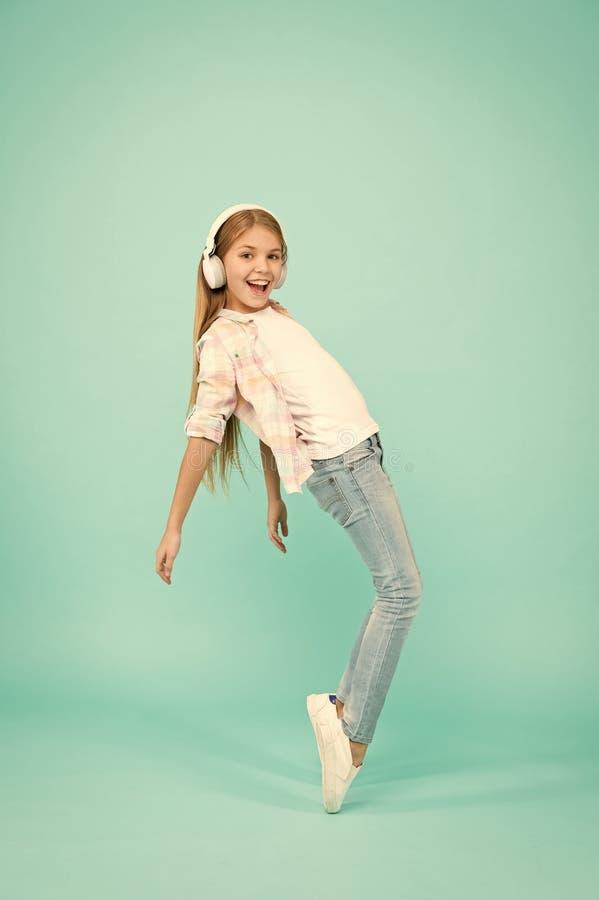 Szcz??liwe piosenki stawia ona w dobrym nastroju dziewczyny dancingowej pojedynczy white Szcz??liwa ma?a dziewczyna tanczy muzyka fotografia stock