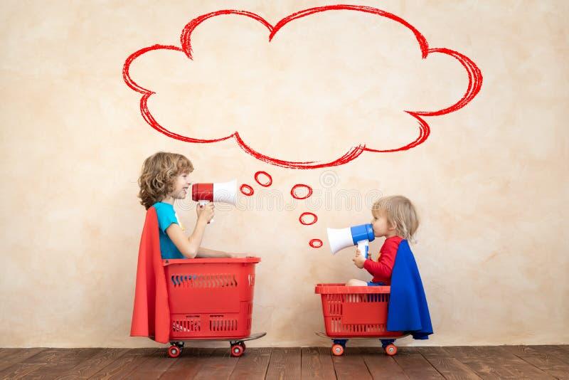 Szcz??liwi dzieci jedzie zabawkarskiego samoch?d w domu obrazy stock