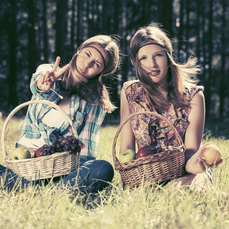 Szcz??liwi potomstwa fasonuj? dziewczyny z owocowym koszem na naturze zdjęcie royalty free