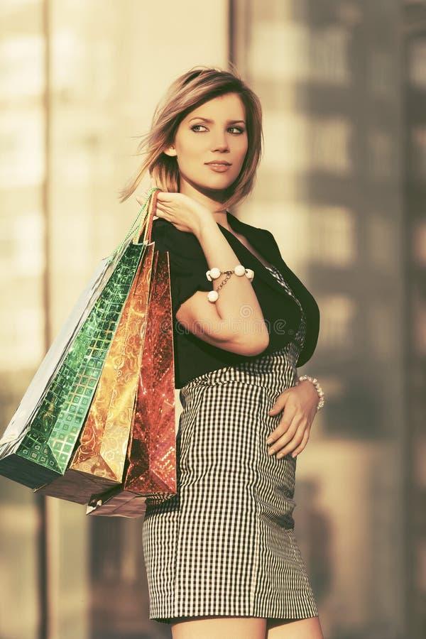Szcz??liwi potomstwa fasonuj? kobiety z torba na zakupy przy centrum handlowym zdjęcia stock