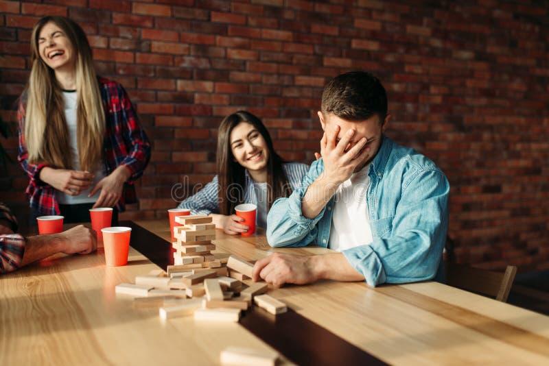 Szcz??liwi przyjaciele bawi? si? sto?ow? gr? przy sto?em w kawiarni fotografia stock