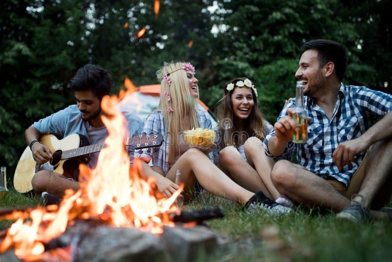 Szcz??liwi przyjaciele cieszy si? muzycznego pobliskiego ognisko przy noc? obrazy stock