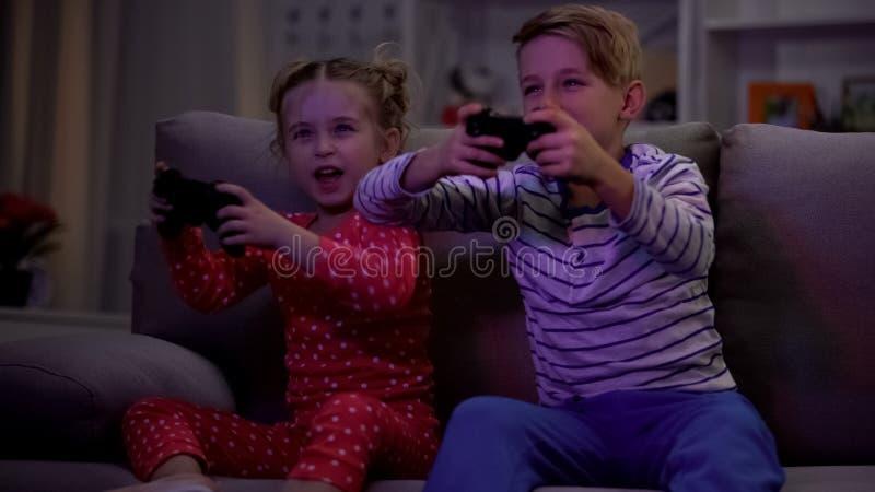 Szcz??liwy brat i siostrzany bawi? si? gra wideo przy nocy siedz?c? kanap?, na??g zdjęcie stock