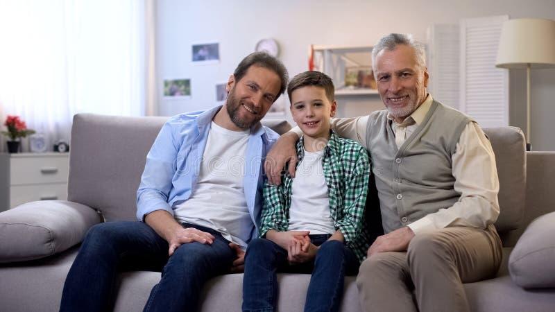 Szcz??liwy dziadunio, tata i syn patrzeje kamera, og?lnospo?eczny ubezpieczenie, szcz??liwa rodzina fotografia royalty free