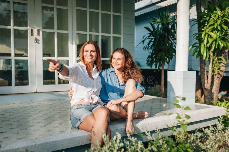 Szcz??liwy lesbian pary obsiadanie na tarasie przy ich domem na wsi zdjęcia royalty free