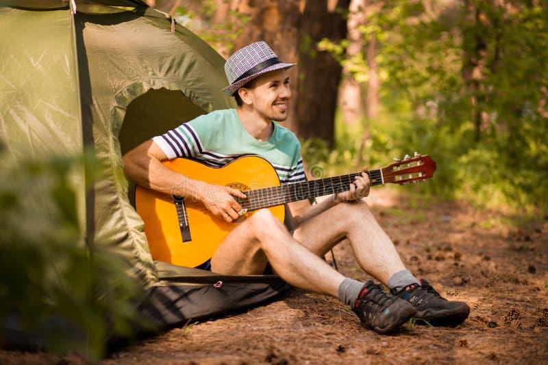 Szcz??liwy m?odego cz?owieka camping i pobrz?ka gitary instrumentaln? muzyk? relaksowa? przeciw t?u lasowy zmierzch zdjęcie stock