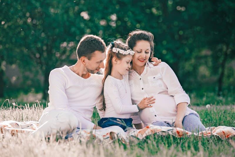 Szcz??liwy rodzinny obsiadanie na trawie na letnim dniu obrazy stock