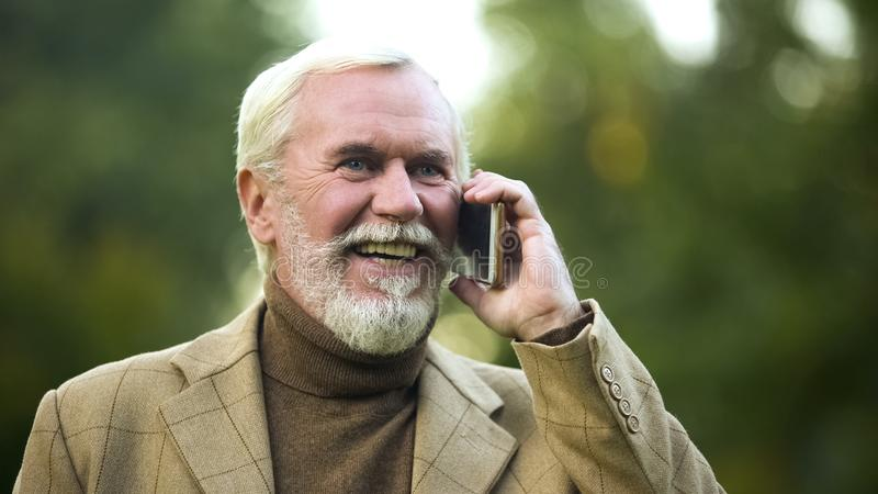 Szcz??liwy starszy m??czyzna opowiada na telefonie w parku, komunikacja mobilna, technologia fotografia royalty free