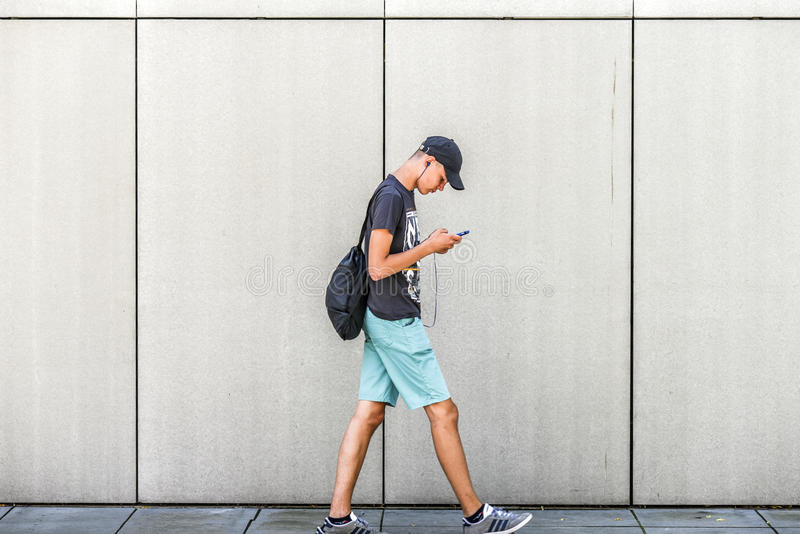 Szczecin, Poland, July 17, 2017: Boy walking down the street and. Writing a message on the phone royalty free stock image