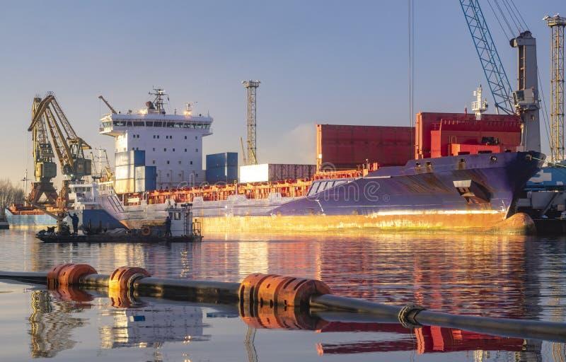 Szczecin, Polen Dezember 2018: Mannschaft des Lastkahnes eine Rohrleitung im Hafen von Szczecin, Polen legend lizenzfreies stockfoto