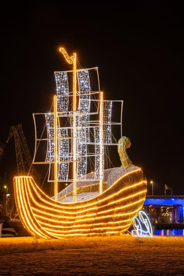 SZCZECIN, POMERANO OCIDENTAL / POLÔNIA - 2018: A marina cai com um iate néon decorativo e uma visão do residencial iluminado fotografia de stock
