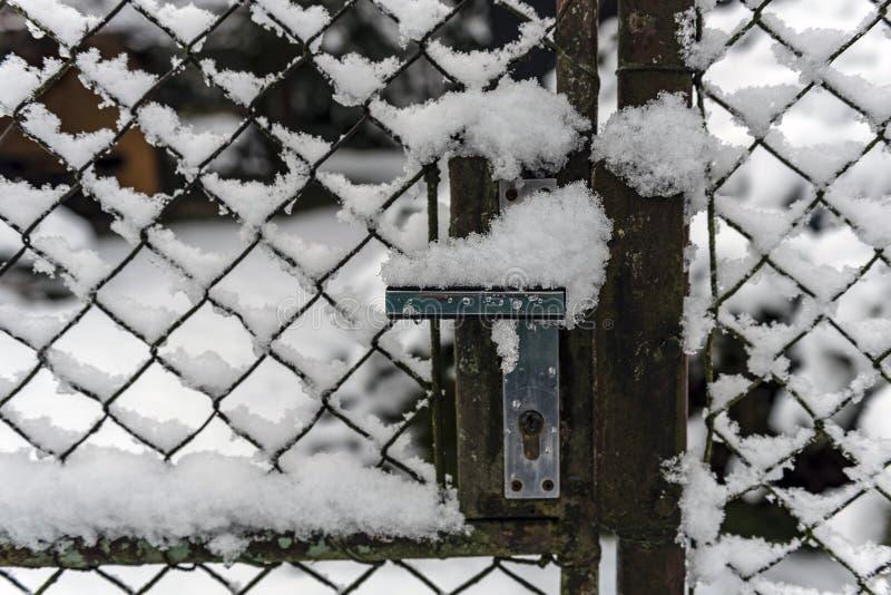Szczegół korba ogrodowa brama zakrywająca z śniegiem obraz stock