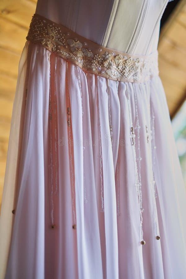 szczegół ślubna suknia na haczyku na drewnianym nakryciu kasetonował ścianę obrazy royalty free