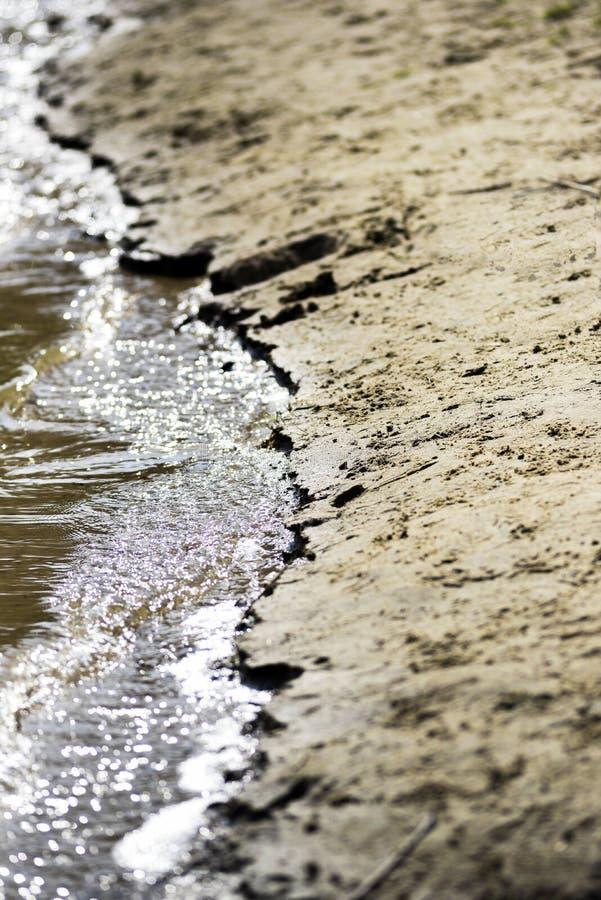 Szczegół brzeg Woda i piasek na słonecznym dniu obrazy royalty free