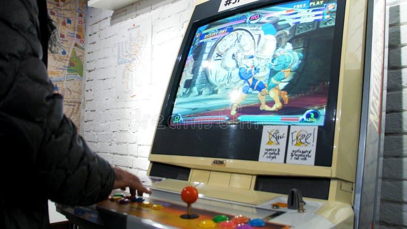 Szczegół gracze wręcza oddziałać wzajemnie i bawić się z joystickami i guzikami na starej arkady grą w hazardu pokoju zdjęcie stock