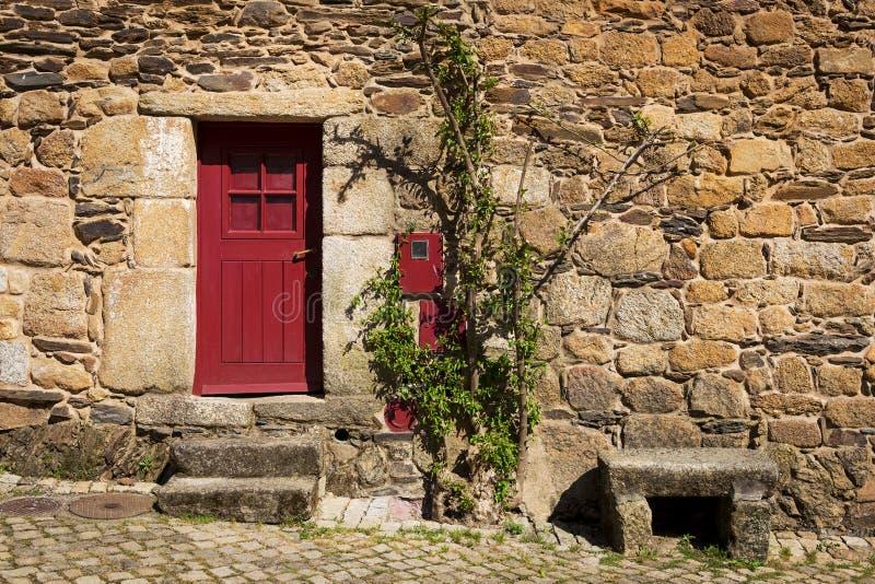 Szczegół kamienny dom z czerwonym drzwi w historycznej wiosce Idanha Velha w Portugalia obraz stock