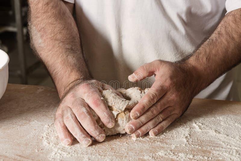 Szczegół na ręki piekarnianym ugniata cieście na czarnej desce z mąka proszkiem Pojęcie pieczenie i ciasto sklepy obrazy royalty free