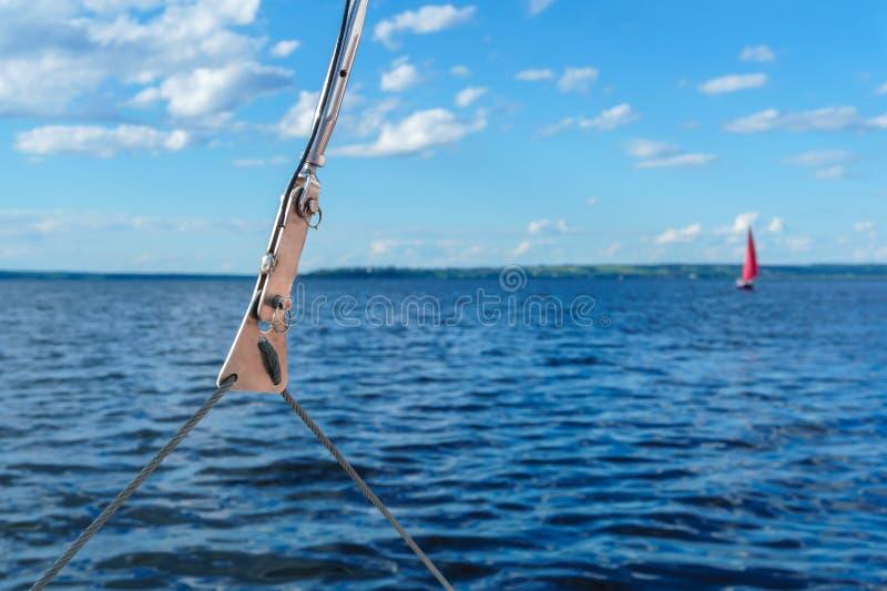 Szczegół olinowanie przeciw w górę tła zamazany morze krajobraz z szkarłatnym żaglem w odległości zdjęcie stock