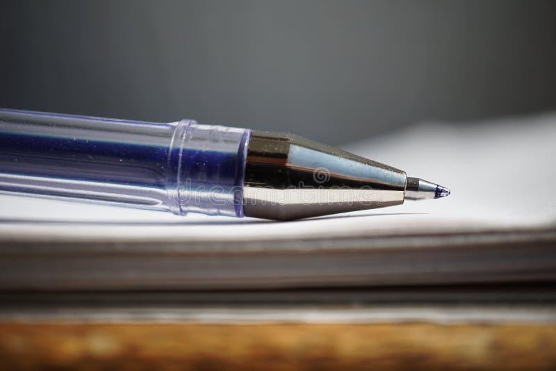 Szczegół ostra porada błękitny balowy pióro na białym prążkowanym notepad jako symbol stacjonarny biznesowy biuro obraz stock