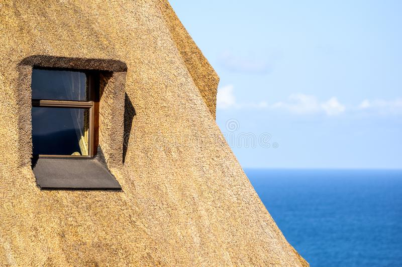 Szczegół pokrywająca strzechą dach domowa używa trzcinowa trawa jako materiał budowlany Windows widoczny i ocean w tle obrazy stock