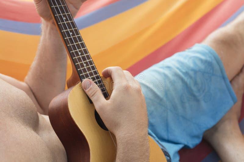 Szczegół relaksuje na hamaku i bawić się ukulele mężczyzna zdjęcie stock