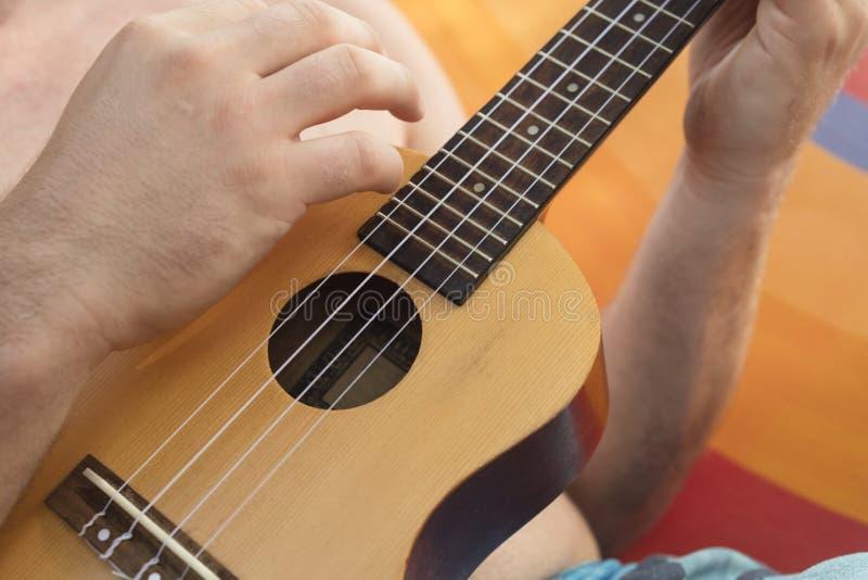 Szczegół relaksuje na hamaku i bawić się ukulele mężczyzna zdjęcie royalty free