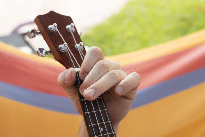 Szczegół relaksuje na hamaku i bawić się ukulele mężczyzna fotografia royalty free