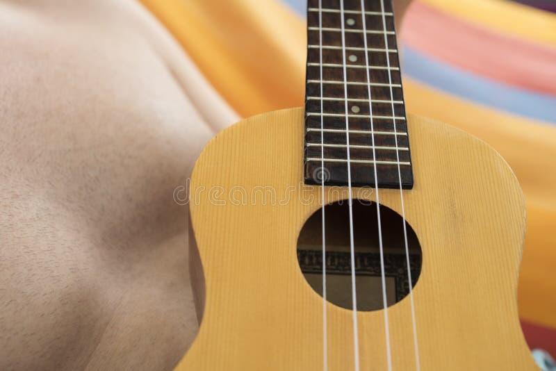 Szczegół relaksuje na hamaku i bawić się ukulele mężczyzna zdjęcia royalty free