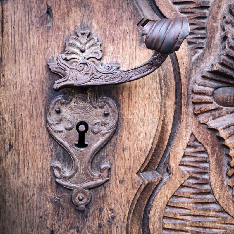 Szczegół rzeźbiący drewniany portal z dokonanego żelaza rękojeścią zdjęcia stock