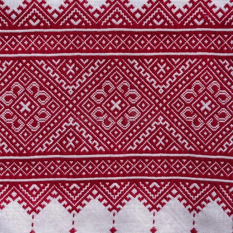 Szczegół upiększony ornament z czerwonymi niciami na białej tkaninie, ukraińska ludowa broderia, zakończenie w górę fotografia stock
